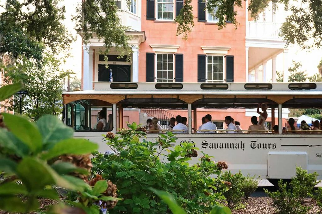 A white Old Savannah Tours trolley passes in front of a salmon-colored mansion at 432 Abercorn Street in Savannah