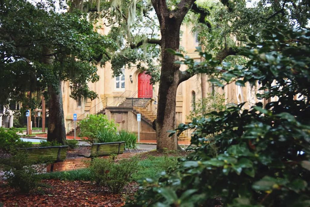 Rain-soaked Calhoun Square in Savannah with Wesley Monumental Church seen in the background.