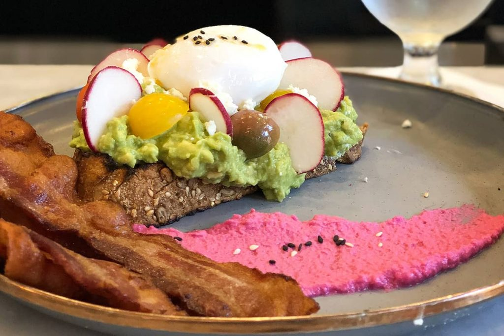 Two slices of crispy bacon, a pinkish beet spread smeared across a dark plate, and avocado toast with an egg and beet topping at The Collins Quarter in Savannah