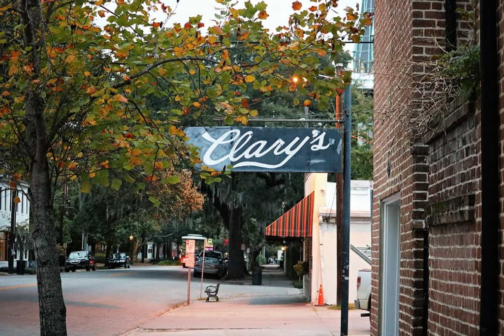 A charming old-timey B&W sign for Clary's Cafe surrounded by trees with fall color