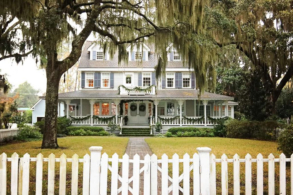 Victorian mansion with dusty blue shutters and a large porch decorated with Christmas greenery, surrounded by large oaks and a white picket fence