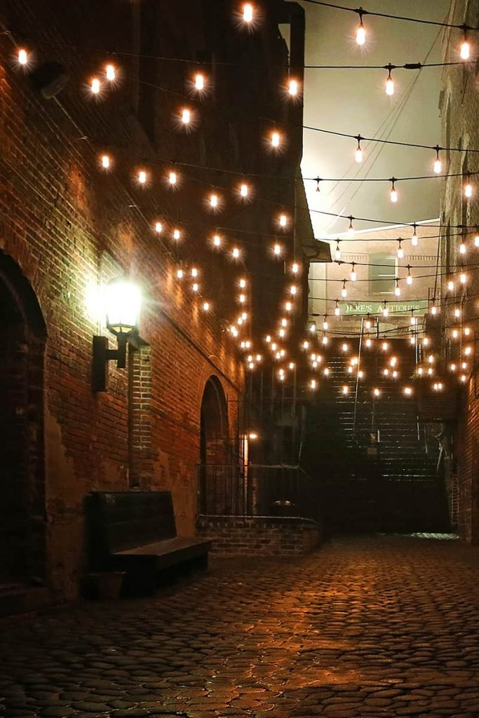 A dark riverfront alleyway dimly lit by twinkle lights leading to haunted Savannah's treacherous Stone Stairs of Death