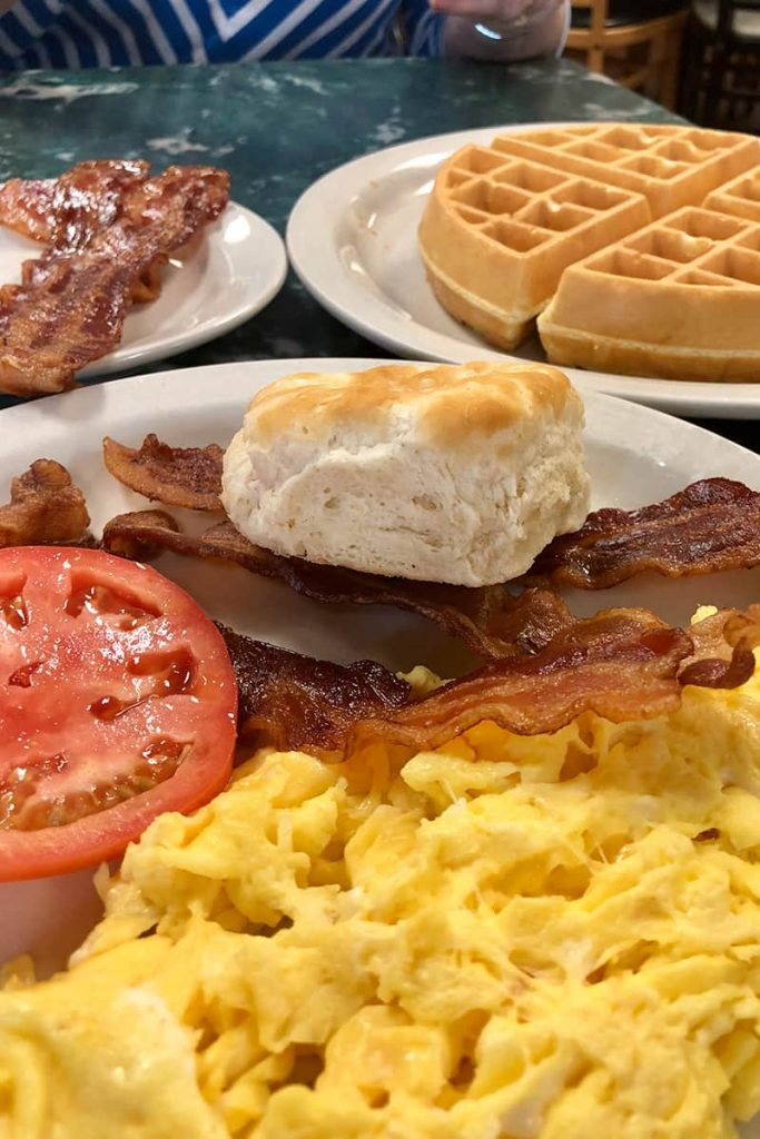 A breakfast plate at Savannah's Clary's Cafe showing hearty portions of scrambled eggs, crispy bacon, waffles, a biscuit, and tomato