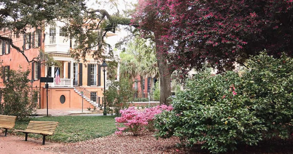 A salmon colored 3-story home in the distance with beautiful landscaping of pink azaleas and large oaks in the foreground