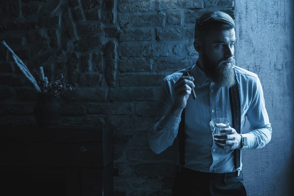 A dapper vampire stands against a fireplace with a drink and cigar in-hand as an eerie blue glow shades the room