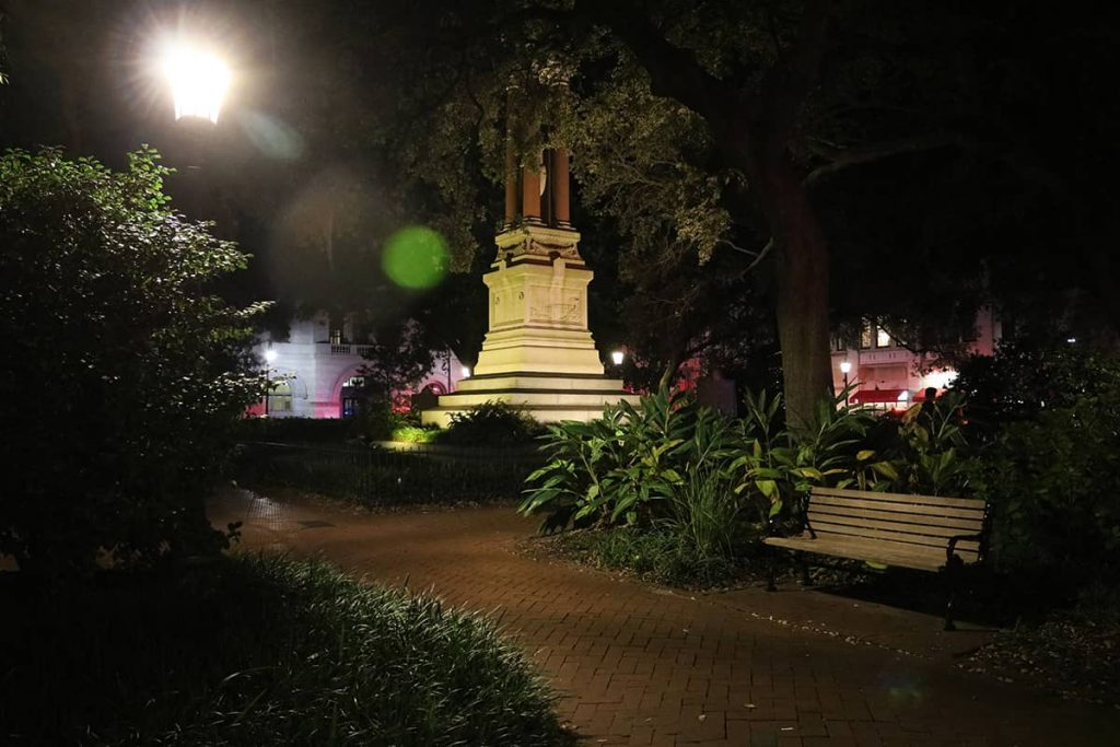 Haunted Wright Square at night with gas lanterns illuminating red brick sidewalks and orbs visible in the photo