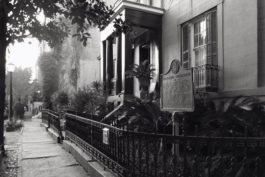 B&W image of the exterior front entrance of the haunted Sorrel-Weed House in Savannah