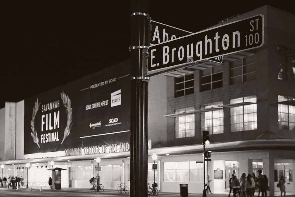 B&W shot of a street corner at night with crowds of people milling about and a large sign that reads Savannah Film Festival