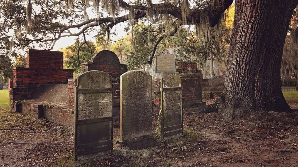A trio of headstones beneath an old oak covered in Spanish moss in Colonial Park Cemetery