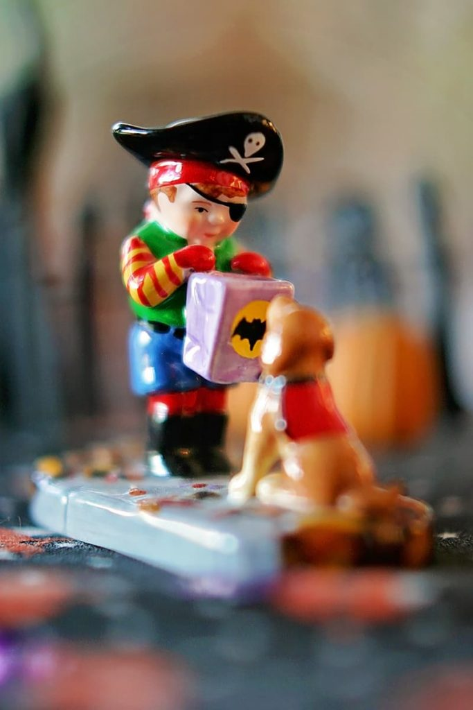Figurine of a young boy dressed as a pirate going trick-or-treating with his dog